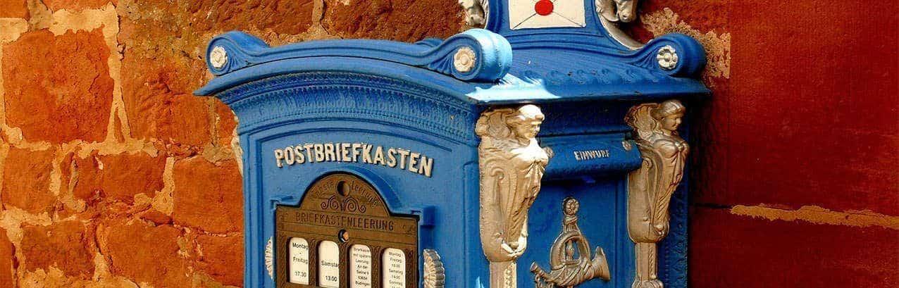 fotografa de un buzón de la epoca victoriana, de color azul con un sobre con lacrado y decoración en los laterales para llamar la atención