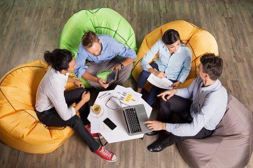 grupo de millenials en círculo reunidos en torno a un ordenador