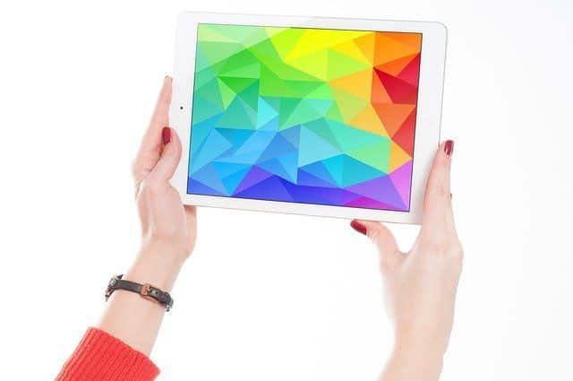 fotografía de unas manos con una tableta que muestra un diseño colorido poligonal