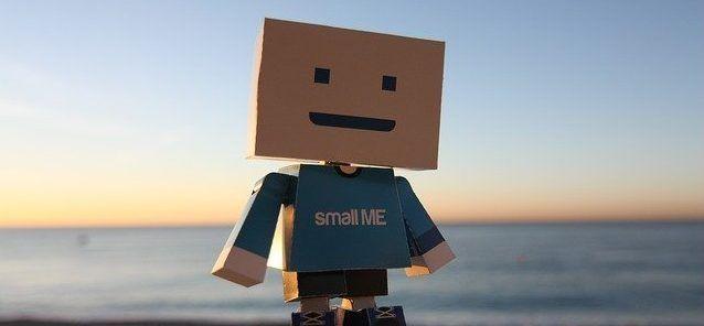 fotografía de un pequeño muñeco de cartón sobre la arena de la playa