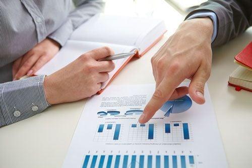 grupo de personas agrupadas analizando los resultados, apuntado con el dedo a un folio con gráficos en color azul